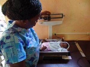 Nurse Saillant weighs baby